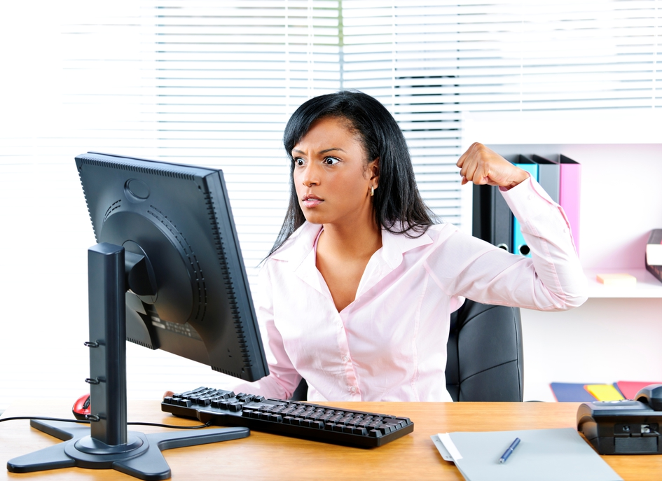 woman making fist at computer in frustration