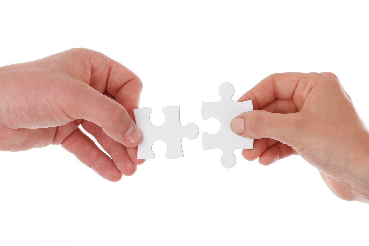 2 hands putting jigsaw pieces together