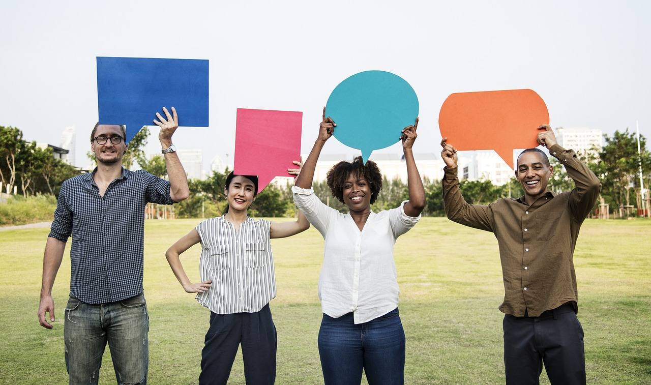 4 people standing in field with quote bubble construction paper cutouts