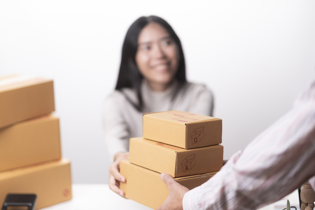 woman handing cardboard boxes to man across table