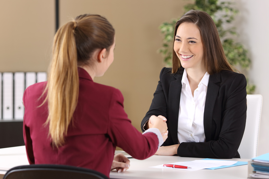 Two businesswomen wearing suits handshaking after signing a contract of a good deal in an office interior