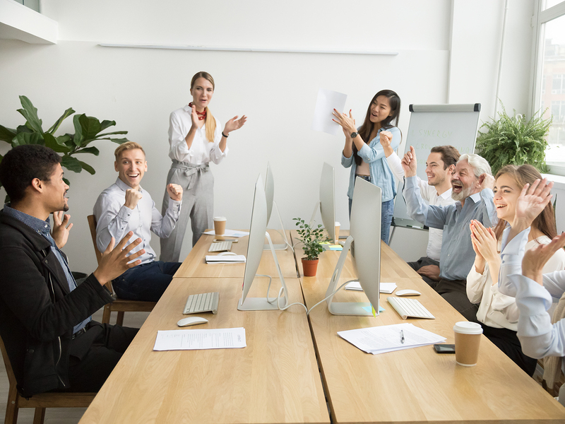 Corporate diverse team colleagues congratulating motivated african coworker with business success or achievement clapping hands in coworking office, multiracial employees applaud excited by good news
