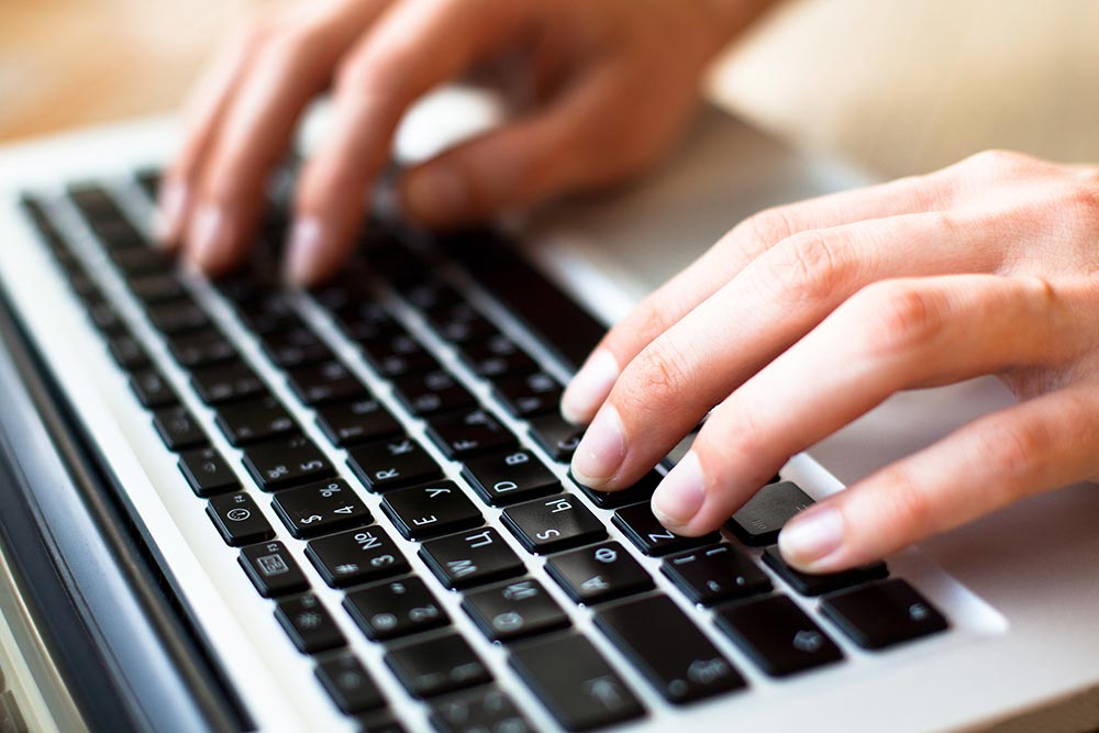 Hands typing text on a laptop keyboard